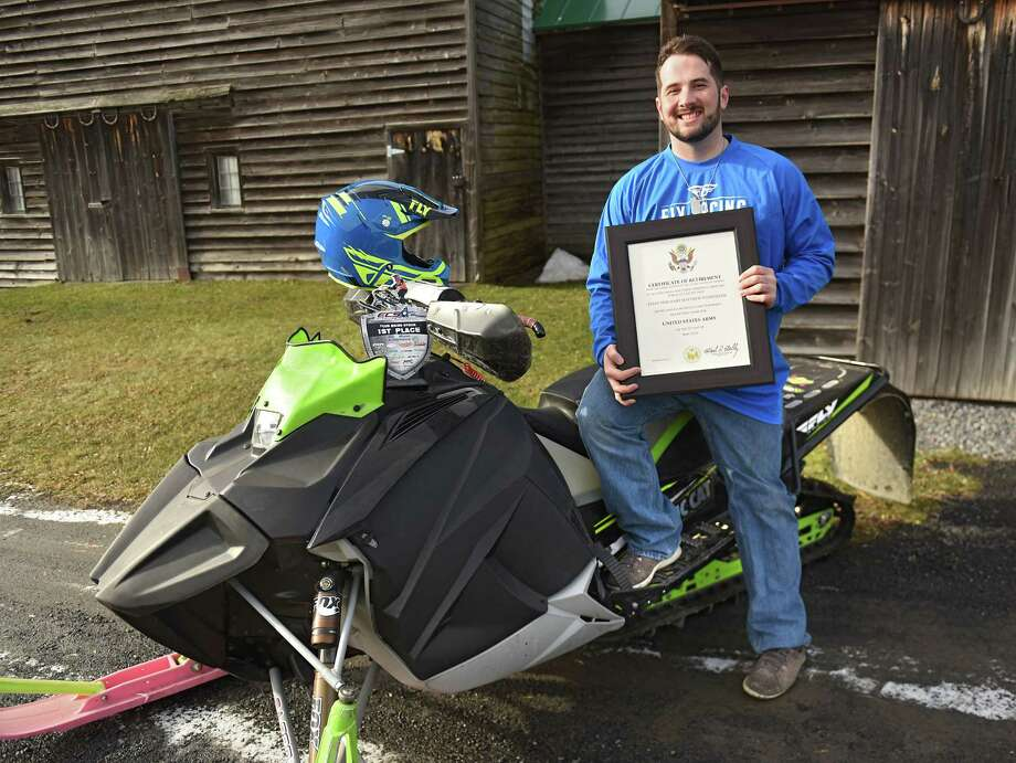 Snowmobile racer Matt Stonesifer holds his certificate of retirement from the United States Army as he sits on his snowmobile at his home on Friday, Jan. 4, 2019 in East Berne, N.Y. (Lori Van Buren/Times Union) Photo: Lori Van Buren, Albany Times Union / 20045767A