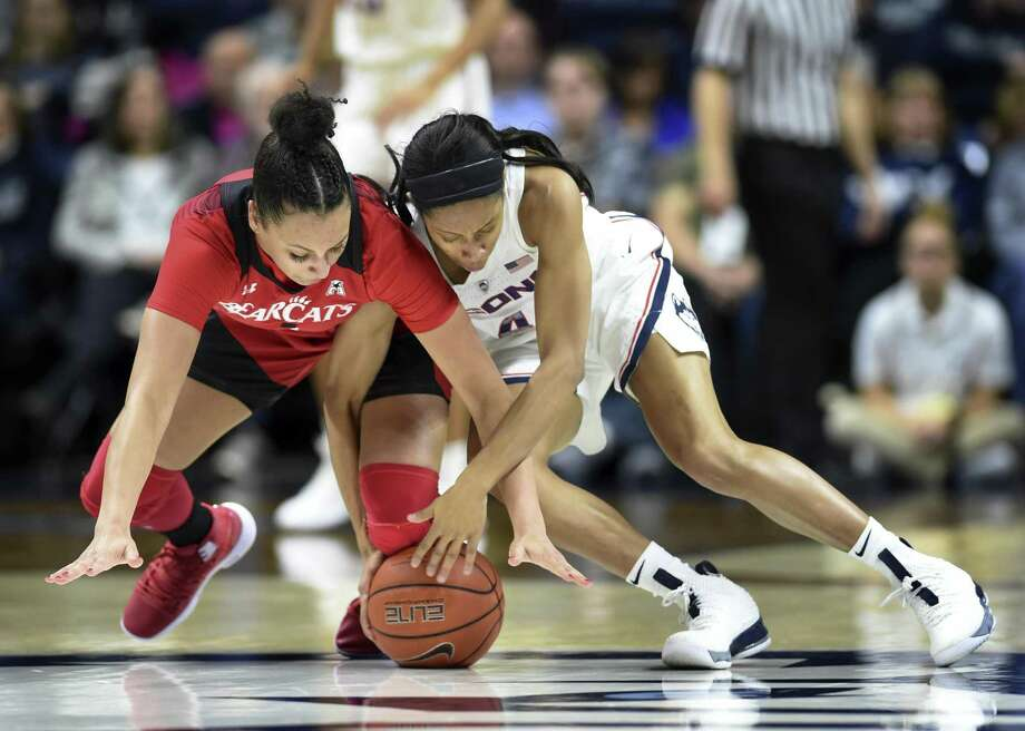 Cincinnati's Angel Rizor (4) and UConn's Mikayla Coombs (4) reach for the ball during the first half of Wednesday's game in Storrs. UConn won 82-38. Photo: Stephen Dunn / Associated Press / Copyright 2019 The Associated Press. All rights reserved