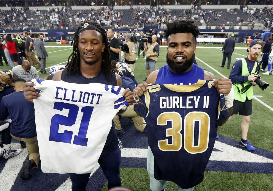 FILE - In this Oct. 1, 2017, file photo, Los Angeles Rams' Todd Gurley, left, and Dallas Cowboys' Ezekiel Elliott, right, swap jerseys after an NFL football game, in Arlington, Texas. Gurley is a big football fan, and Elliott is one of his favorite players. The good feelings are mutual heading into the Cowboys' playoff visit to the Rams and a showdown between the NFL's two premiere running backs. (AP Photo/Michael Ainsworth, File) Photo: Michael Ainsworth, Associated Press