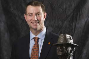 "Clemson coach Dabo Swinney poses for a photograph with the Paul ""Bear"" Bryant Coach of the Year Award, before the ceremony Wednesday, Jan. 9, 2019, in Houston. (Yi-Chin Lee/Houston Chronicle via AP)"