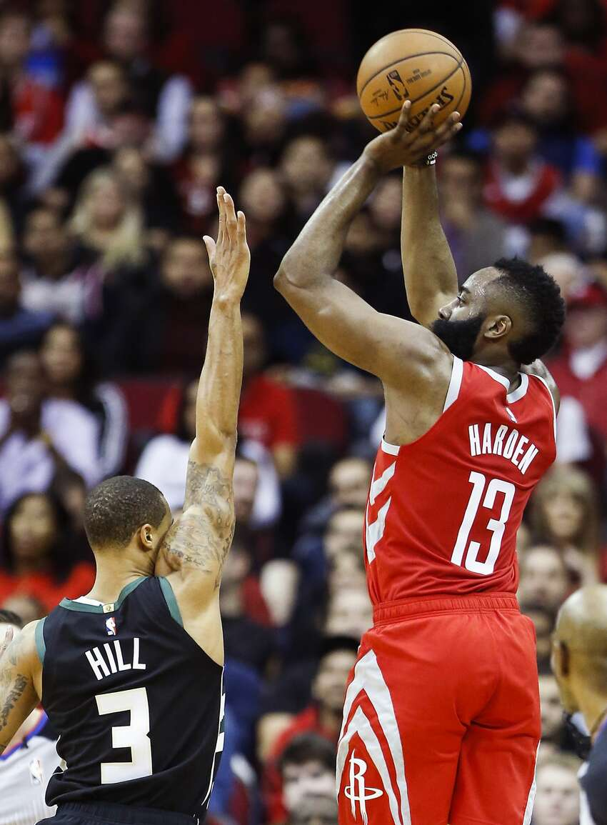 Houston Rockets guard James Harden (13) takes a 3-point shot over Milwaukee Bucks guard George Hill (3) during the first half of an NBA basketball game at Toyota Center on Wednesday, Jan. 9, 2019, in Houston.