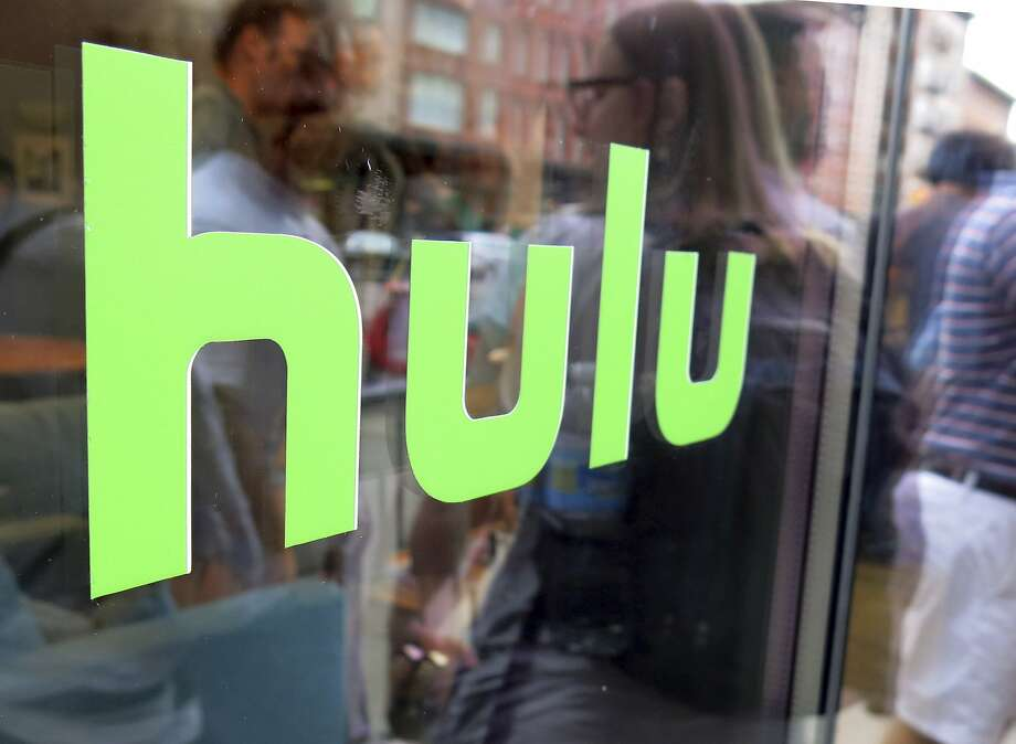 "FILE - This June 27, 2015, file photo, shows the Hulu logo on a window at the Milk Studios space in New York. To get a full slate of programming, TV watchers may soon have to subscribe to several services instead of just one or two. Among those options will be services like Netflix and Hulu that offer a wide range of video from a variety of sources; cable-like ""skinny bundles"" such as FuboTV, Sling and YouTube TV that offer a variety of live channels; and channel- or network-specific services like Disney Plus. (AP Photo/Dan Goodman, File) Photo: Dan Goodman, Associated Press"