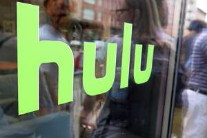 "FILE - This June 27, 2015, file photo, shows the Hulu logo on a window at the Milk Studios space in New York. To get a full slate of programming, TV watchers may soon have to subscribe to several services instead of just one or two. Among those options will be services like Netflix and Hulu that offer a wide range of video from a variety of sources; cable-like ""skinny bundles"" such as FuboTV, Sling and YouTube TV that offer a variety of live channels; and channel- or network-specific services like Disney Plus. (AP Photo/Dan Goodman, File)"