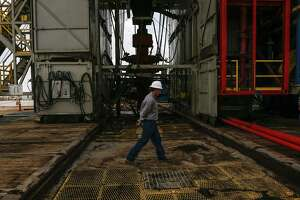A worker walks across a pad site where a drilling rig will create three to six wells next to each other at a Chevron drilling and hydraulic fracturing site.