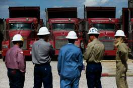 People stand in front of trucks at a Chevron hydraulic fracturing site.