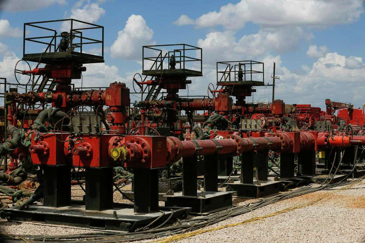 Pressure pumps wait for hydraulic fracturing operations to begin at a Chevron drilling site in the Permian Basin.