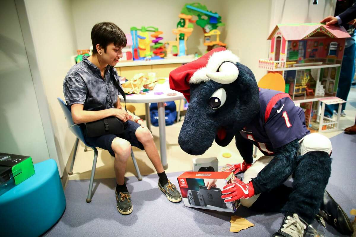 The Houston Texans' Toro has a portable game for a patient at Texas Children's Hospital in the Medical Center. The Houston Texans and Conn's HomePlus donated mobile gaming stations to provide entertainment for children unable to visit the hospital playrooms.