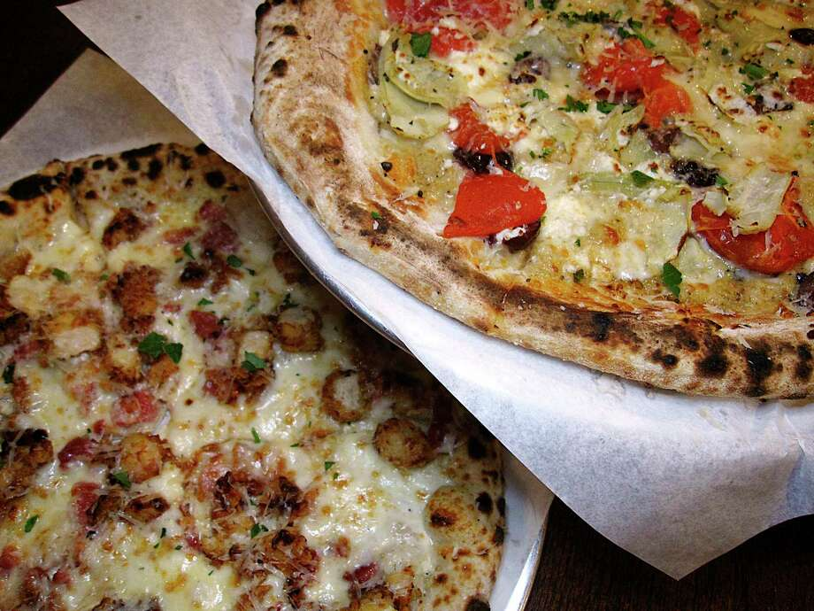 Greek pizza (top) with artichoke, baba ghanoush, feta cheese, olives and dried tomatoes and a Chicken Bacon Ranch pizza with fried chicken, ranch dressing, bacon and mozzarella from SoHill Cafe. Photo: Mike Sutter /Staff
