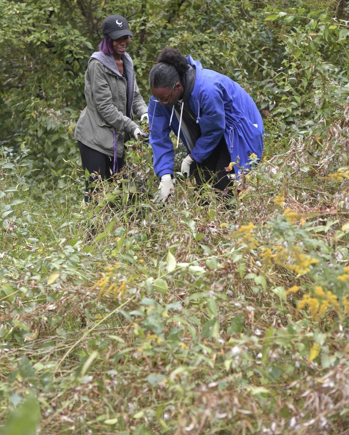 Franaja Payne-Smith, right, and Asia Henderson work along the Norwalk River Valley Trail clearing debris and invasive plants on September 30, 2017, in Ridgefield, Conn.