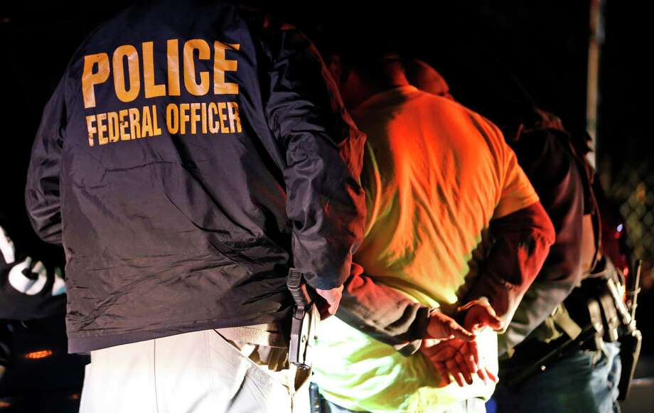 In this Oct. 22, 2018, photo U.S. Immigration and Customs Enforcement agents surround and detain a person during a raid in Richmond, Va. ICE's enforcement and removal operations, like the five-person field office team outside Richmond, hunt people in the U.S. illegally, some of whom have been here for decades, working and raising families. Carrying out President Donald Trump's hard-line immigration policies has exposed ICE to unprecedented public scrutiny and criticism, even though officers say they're doing largely the same job they did before the election, prioritizing criminals. Photo: Steve Helber, AP / Copyright 2018 The Associated Press. All rights reserved.
