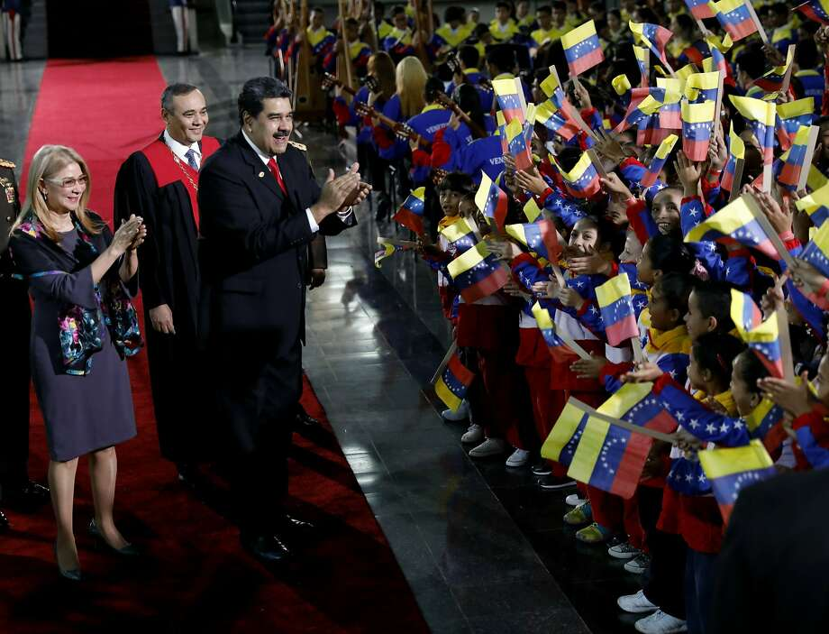 Venezuela President Nicolas Maduro and first lady Cilia Flores stop to greet flag-waving children upon arrival to the Supreme Court for Maduro's inauguration ceremony in Caracas. Photo: Ariana Cubillos / Associated Press