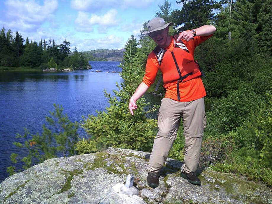 "A boy scout of Edwardsville Troop 31 points to a survey marker designating the US/Canadian border following a recent 110-mile canoe trip in boundary waters. A currently forming girl's group, Troop 27, will be able to experience similar adventures through Boy Scouts of America's new Scouts BSA program. Troop 31 is preparing to be a ""sister"" group to Troop 27 under the initiative. Photo: For The Intelligencer"