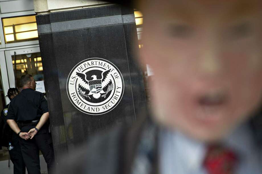 The Immigration and Customs Enforcement (ICE) headquarters stands past a demonstrator wearing a mask resembling U.S. President Donald Trump during a protest against detaining and separating immigrant families in Washington, D.C., U.S., on Wednesday, June 27, 2018. A federal judge today ordered the U.S. to reunite immigrant children who were separated from their families at border crossings and to stop detaining parents without their children, prompting a new call for Congress to pass an immigration law from the president. Photographer: Andrew Harrer/Bloomberg Photo: Andrew Harrer, Bloomberg News Service / © 2018 Bloomberg Finance LP