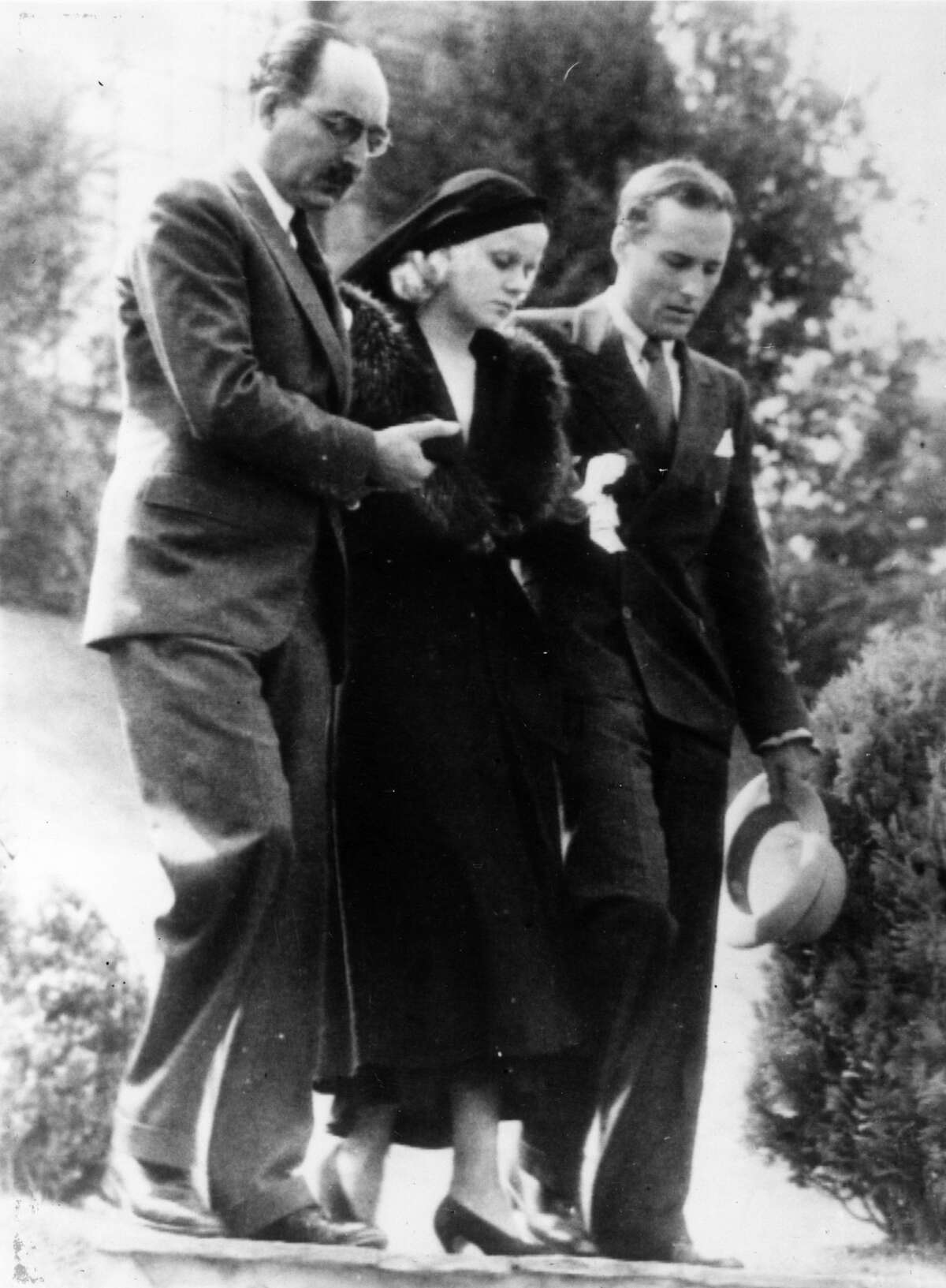 Jean Harlow being assisted from her house by her step-father Mario Bello and a relative Donald Robertson on her way to the funeral of her husband Paul Bern, who was found shot dead at his Beverly Hills home in 1932.