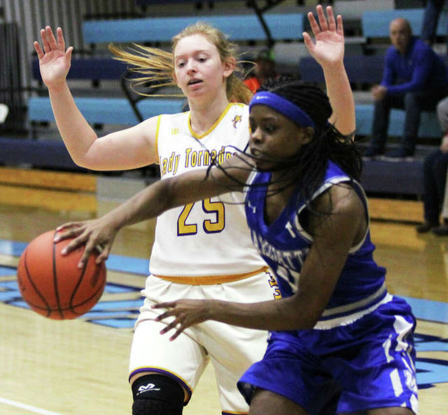 Marquette Catholic's Adrenna Snipes (right), shown passing to a teammate while being defended by Taylorville's Xanna Tomasello in a Dec. 27 game at the Jersey Tourney, had 14 points and nine steals in the Explorers' victory Wednesday night at Madison. Photo: Greg Shashack / The Telegraph