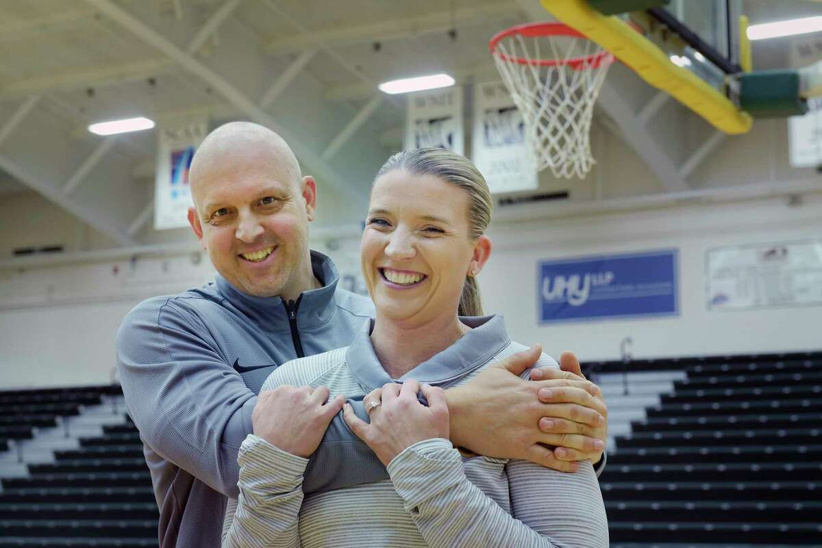 Ali Jaques, foreground, Siena women's basketball coach, and her fiancé, Marc Rybczyk, Niagara men's assistant coach, pose for a photo at the Marcelle Athletic Complex at Siena College on Thursday, Jan. 10, 2019, in Loudonville, N.Y. Jaques and Rybczyk got engaged in August. Rybczyk found out this fall he has stage 4 cancer. He's undergoing treatment and living with Jaques while taking a leave from his coaching job. (Paul Buckowski/Times Union)