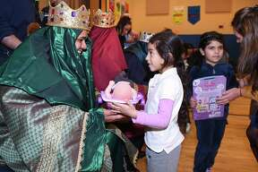 New Haven Fire Department Lt. Ian Cordero (left) gives kindergartener Hilana Nava, 5, a gift at a Three Kings Day event at Clinton Avenue School in New Haven on January 10, 2019. The New Haven Hispanic Firefighters Association funded presents for 300 students and organized the event.
