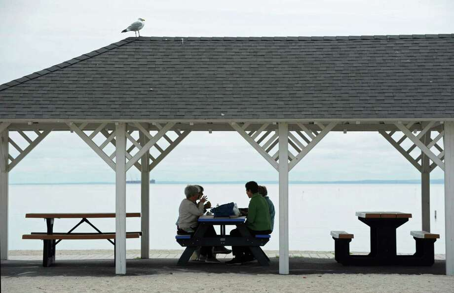 Beachgoers have lunch under the pavillion and partly cloudy skies at Compo Beach on May 10. Photo: Erik Trautmann / Hearst Connecticut Media / Norwalk Hour