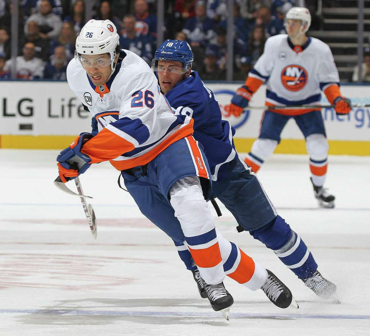 The Islanders Josh Ho-Sangskates away from a checking Andreas Johnsson of the Maple Leafs on Dec. 29 in Toronto.