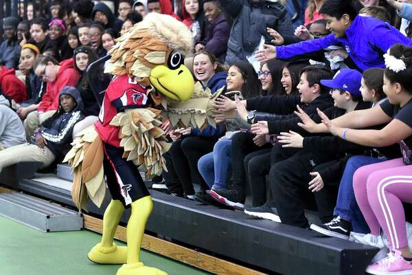 Freddie Falcon, the Atlanta Falcons mascot, mingles with students from Carrigan Intermediate School of West Haven during the Walter Camp Staying in School Rally at the Floyd Little Athletic Center in New Haven on January 10, 2019.