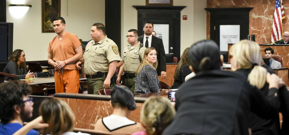 The mother of one of the homicide victims, pictured on the right, yells at Juan David Ortiz as he leaves his arraignment hearing in the 406th District Court on Thursday, Jan. 10, 2019.