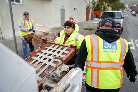 Public Works employees Byron Paz (left), Alberto Bustamante and George Preciado load illegally dumped garbage into a Recology truck in the Bayview district. Photo: Amy Osborne / Special To The Chronicle