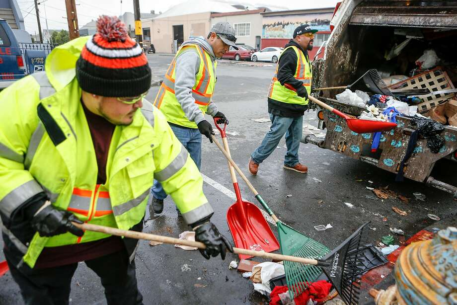 Department of Public Works employees Alberto Bustamante (left), Byron Paz and George Preciado scoop illegally dumped garbage into a Recology truck in San Francisco's Bayview neighborhood. Photo: Photos By Amy Osborne / Special To The Chronicle
