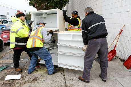 Alberto Bustamante (left), Byron Paz, and George Preciado work with Recology truck driver Roberto Zamudio to clear up trash. Photo: Amy Osborne / Special To The Chronicle