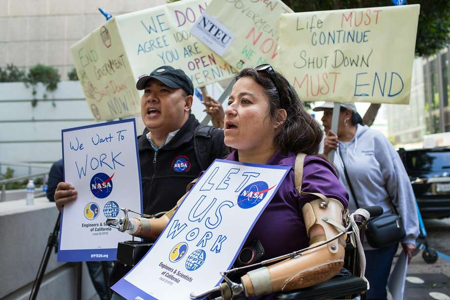 Dana Bolles and Jonas Dino employees of NASA Ames Research Center in Mountain View rally outside the EPA Region 9 Offices in San Francisco on Thursday, Jan. 10, 2019, to protest the continuing shutdown of the government that will keep them from being paid on Friday, Jan. 11, 2019. Photo: Jana Asenbrennerova / Special To The Chronicle