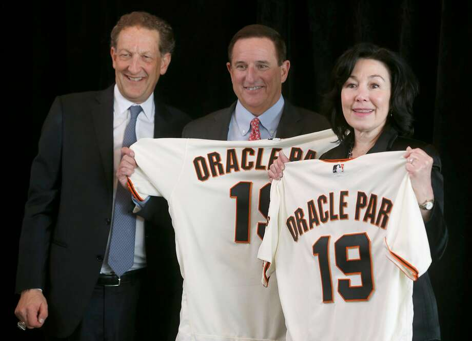 Giants president and CEO Larry Baer (left) presents personalized jerseys to Oracle CEOs Mark Hurd and Safra Catz at a news conference to announce that the name of team's ballpark will become Oracle Park in San Francisco, Calif. on Thursday, Jan. 10, 2019 ending a longterm relationship with AT&T. Photo: Paul Chinn / The Chronicle