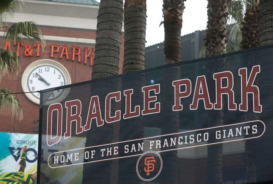 A crew from a sign company hangs a temporary banner in Willie Mays Plaza bearing the new name of the ballpark where the Giants play before the team announced that AT&T Park will be renamed Oracle Park in San Francisco, Calif. on Thursday, Jan. 10 2019. Photo: Paul Chinn / The Chronicle
