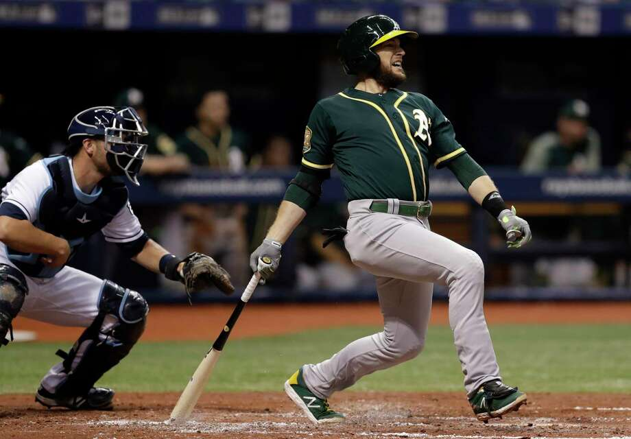 FILE - In this Sept. 15, 2018, file photo, Oakland Athletics' Jed Lowrie, right, lines an RBI-single off Tampa Bay Rays pitcher Yonny Chirinos as Rays catcher Nick Ciuffo, left, looks on during the third inning of a baseball game in St. Petersburg, Fla. A person familiar with the negotiations tells The Associated Press that free agent Lowie and the New York Mets have agreed to a $20 million, two-year contract. The person spoke on condition of anonymity Thursday, Jan. 10, 2019, because the agreement is subject to a successful physical. Photo: Chris O'Meara, AP / Copyright 2018 The Associated Press. All rights reserved.