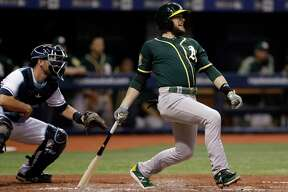 FILE - In this Sept. 15, 2018, file photo, Oakland Athletics' Jed Lowrie, right, lines an RBI-single off Tampa Bay Rays pitcher Yonny Chirinos as Rays catcher Nick Ciuffo, left, looks on during the third inning of a baseball game in St. Petersburg, Fla. A person familiar with the negotiations tells The Associated Press that free agent Lowie and the New York Mets have agreed to a $20 million, two-year contract. The person spoke on condition of anonymity Thursday, Jan. 10, 2019, because the agreement is subject to a successful physical.