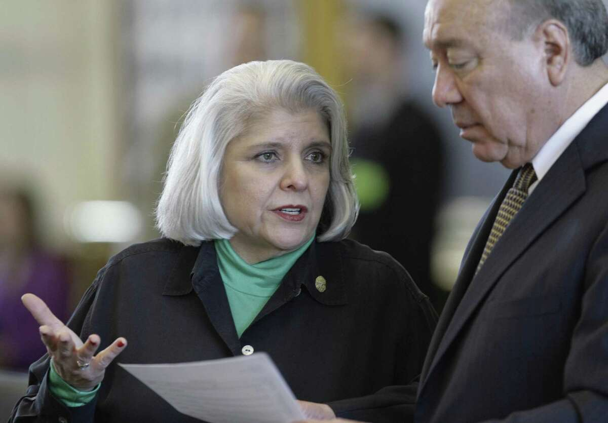 Sen. Judith Zaffirini, D-Laredo, left - talking with Sen. Juan Hinojosa, D-McAllen - has sponsored legislation to protect domestic abuse victims from bad credit imposed by their victimizers.