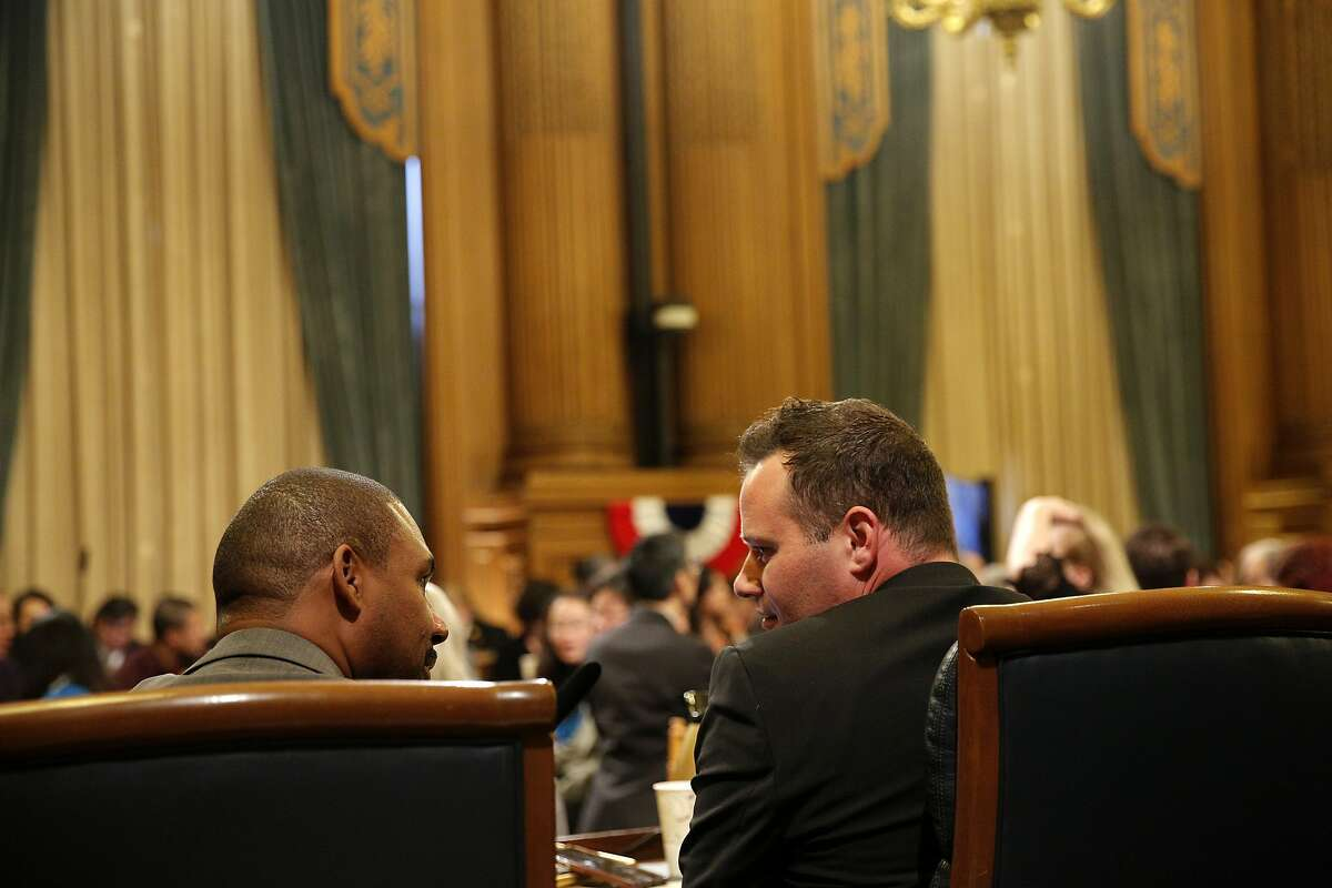 From left: District 10 supervisor Shamann Walton and District 6 Matt Haney supervisor chat during public comment before the board elects a new president for the Board of Supervisors at City Hall on Tuesday, Jan. 8, 2019, in San Francisco, Calif.