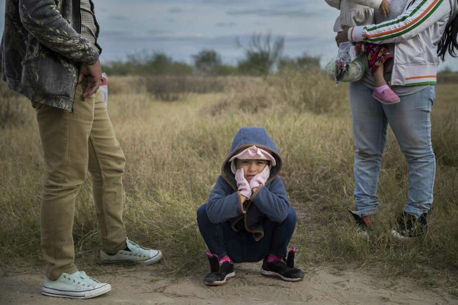 A 6-year-old girl waits with her father for Border Patrol agents to process them near McAllen last month. The number of immigrant families crossing the border, mostly from Guatemala, El Salvador and Honduras, have reached record levels in the past four months, but experts say a wall would not stop them as they turn themselves in, and don't run away.