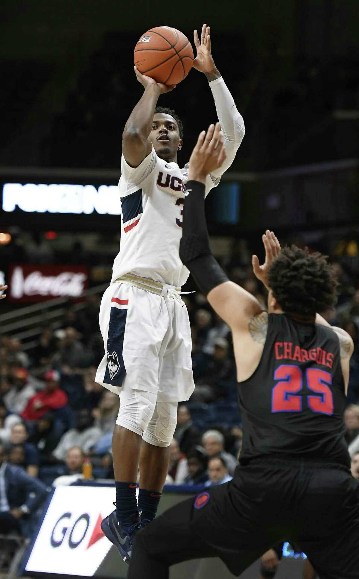 UConn's Alterique Gilbert, top, shoots over SMU's Ethan Chargois during Thursday night's game in Storrs.
