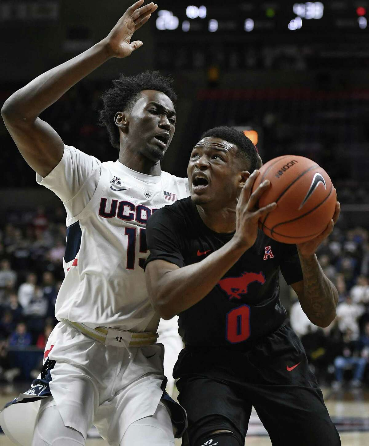 SMU's Jahmal McMurray, right, looks to shoot while defended by UConn's Sidney Wilson, left, defends, on Thursday night in Storrs.