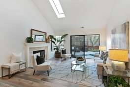 The living room of the Alameda home features a skylight, wood-burning fireplace and access to the backyard.