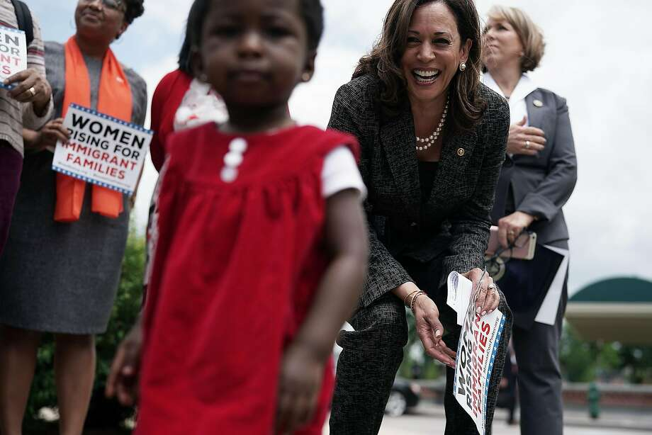 Harris plays with 18-month-old Hawa Tembe, whose mother is an immigrant from Mozambique, during a May news conference on immigration. Photo: Alex Wong / Getty Images 2018