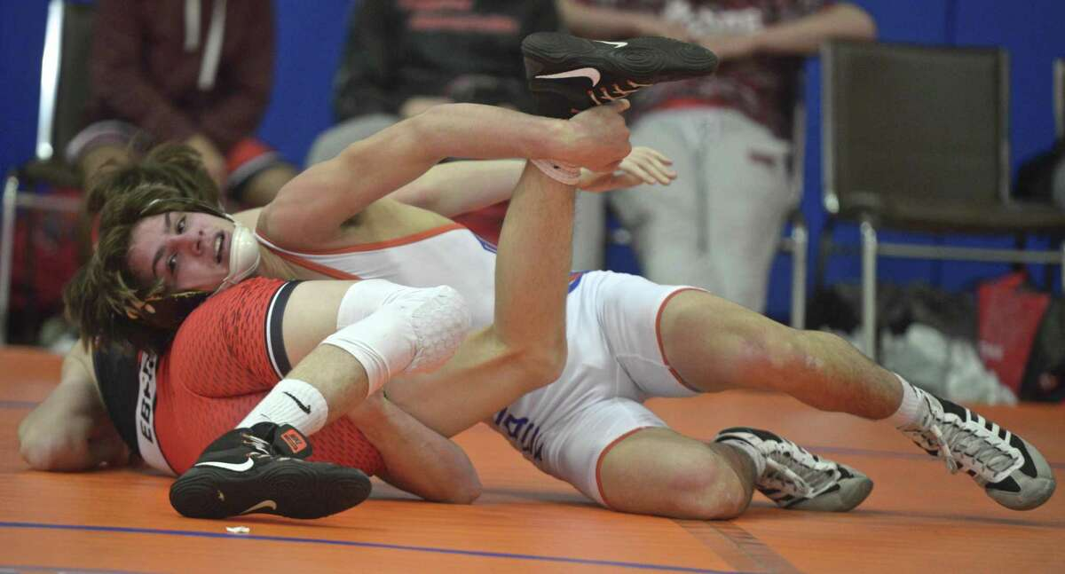 Fairfield-Warde's William Ebert (red) and Danbury's Ryan Jack wrestle in the 126-pound weight class during a dual meet on Dec. 19 at Danbury High School.