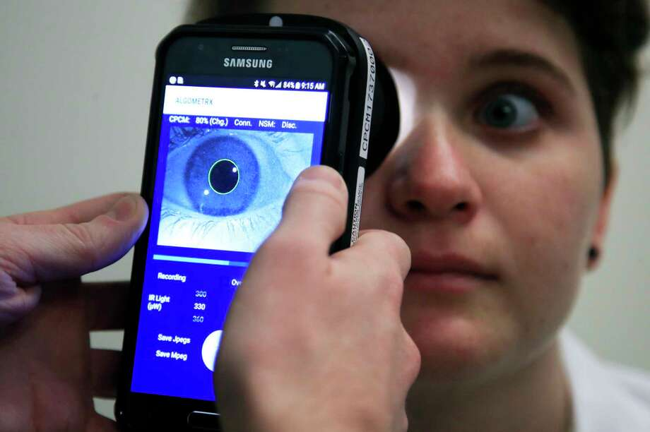 Clinical Research Assistant Kevin Jackson uses AlgometRx Platform Technology on Sarah Taylor's eyes to measure her degree of pain at the Children's National Medical Center in Washington, Monday, Dec. 10, 2018. Children's National Medical Center is testing an experimental device that aims to measure pain according to how pupils react to certain stimuli. (AP Photo/Manuel Balce Ceneta) Photo: Manuel Balce Ceneta / Copyright 2018 The Associated Press. All rights reserved.