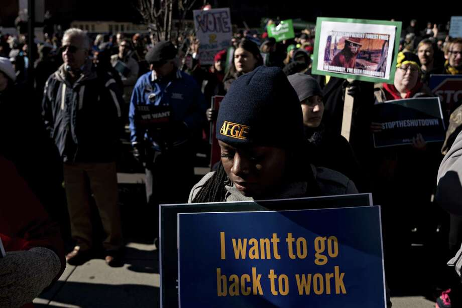 "A demonstrator holds a ""I want to go back to work"" sign during a rally with union members and federal employees to end the partial government shutdown outside AFL-CIO headquarters in Washington, on Thursday. Photo: Bloomberg Photo By Andrew Harrer / Bloomberg"
