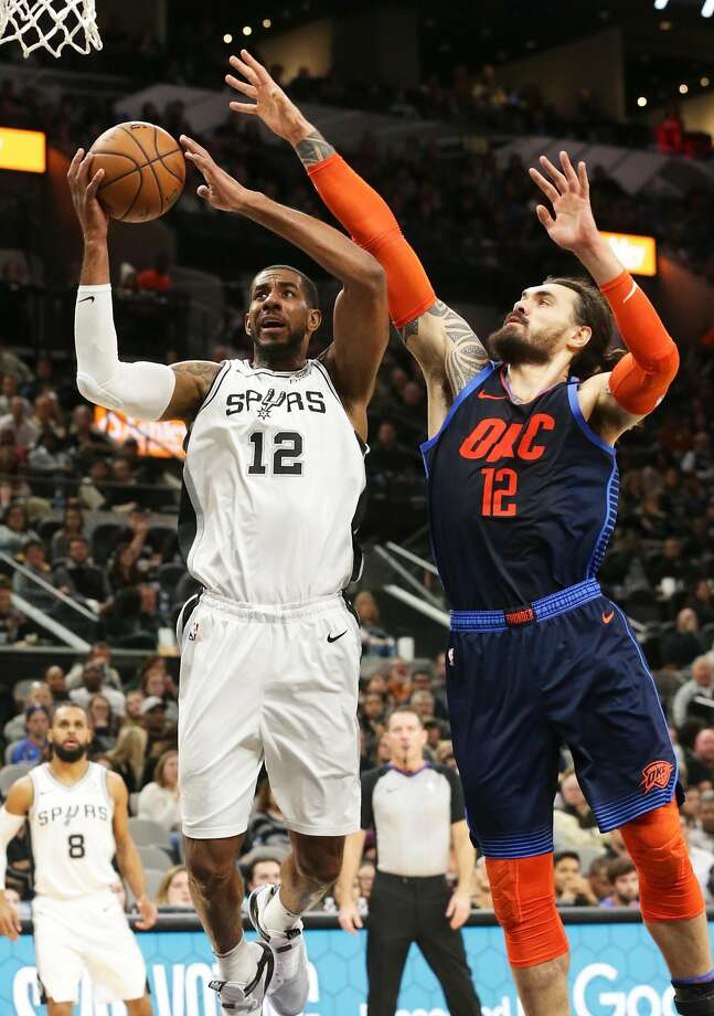 San Antonio's LaMarcus Aldridge lays in a shot over Steven Adams in the Spurs' overtime victory over Oklahoma City. Photo: Tom Reel / San Antonio Express-News