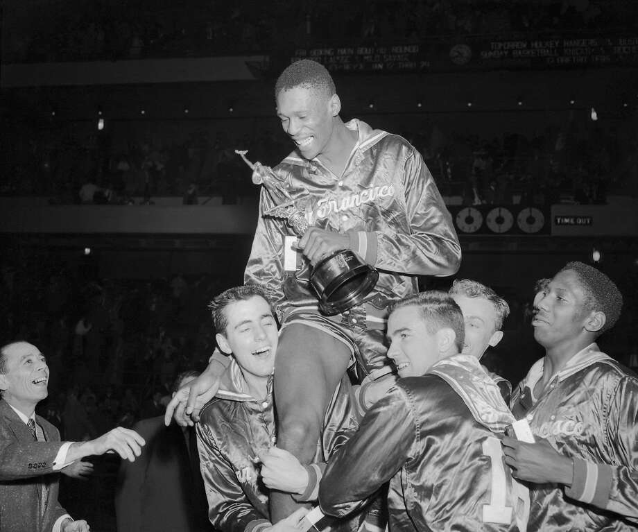 (Original Caption) San Francisco teammates raise big Bill Russell on their shoulders in a spontaneous gesture of acclaim following tonight's triumph over the clans, 70-53, for their holiday festival championship at the garden named the tournament's most valuable player, the 6 foot 10 inch center scored 17 points to pace the dons to their 36th victory grinning broadly Big Bill holds the Tourney's Trophy. Photo: Bettmann Archive