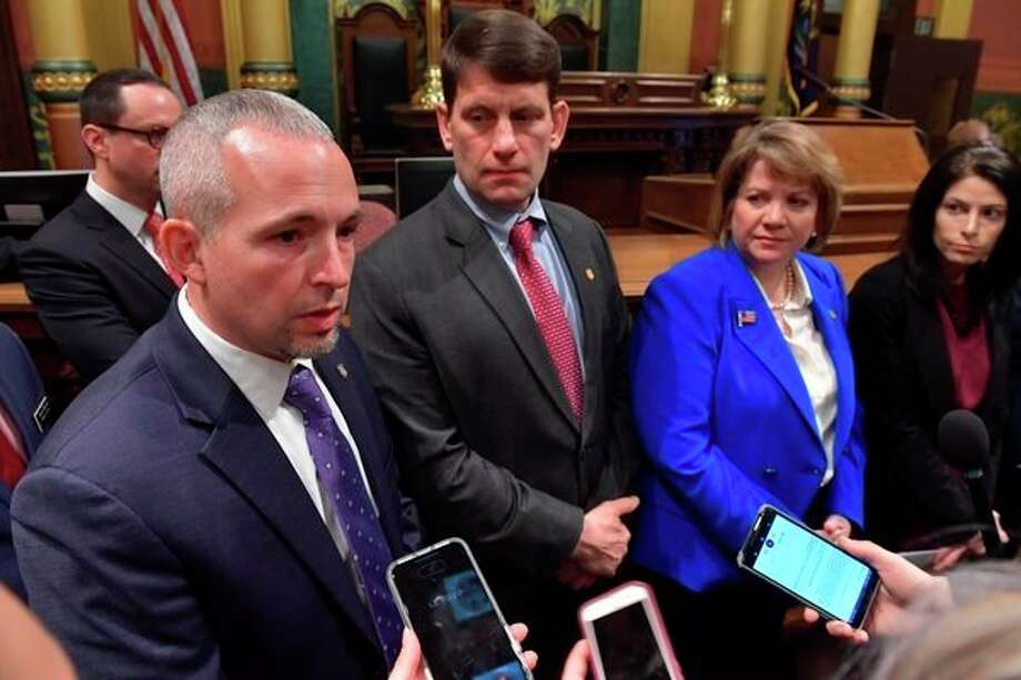 State Rep. Jason Wentworth of Clare, left, discusses his civil asset forfeiture reform plan during a press conference Wednesday on the House floor. He was joined, from left, by Rep. David LaGrand, Minority Leader Christine Greig and Attorney General Dana Nessel, as well as House Speaker Lee Chatfield (not pictured). (Photo provided)