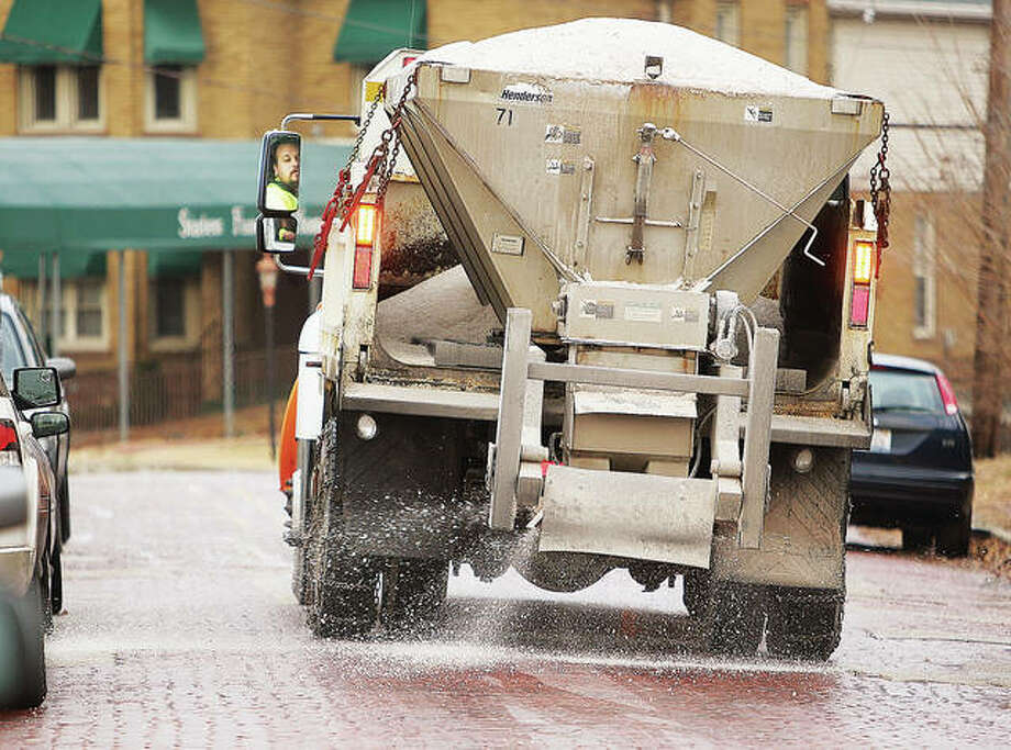 An Alton Public Works snow plow driver uses his mirror, left, to carefully back down Court Street in Alton to salt the roadway ahead of past winter weather. Photo: John Badman | The Telegraph