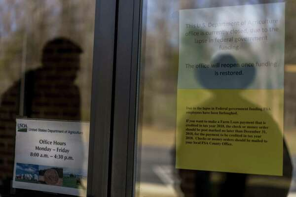 A sign regarding the partial shutdown is posted on the door at a closed USDA office in Boydton, Va. MUST CREDIT: Washington Post photo by Melina Mara