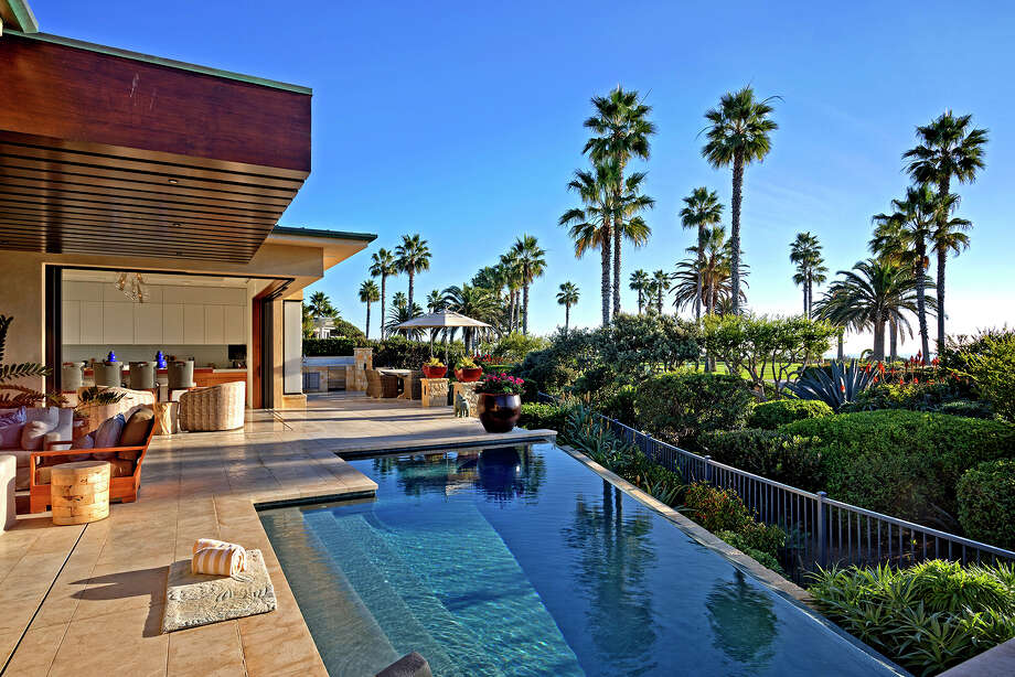 NBA franchise owner Mark Cuban's new home in a Laguna Beach, Calif., resort community makes the most of its ocean view with bi-folding walls of glass and a wealth of outdoor living space. A lower level of the 7,900-square-foot home is set up for entertaining with a wall of flatscreen TVs, a bar and a wine cellar. (Andrew Bramasco/TNS) Photo: Andrew Bramasco / Los Angeles Times
