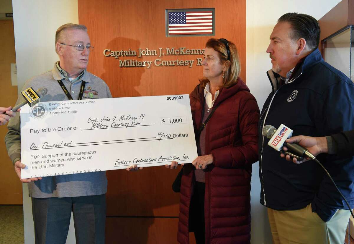 Todd Helfrich, President and CEO of The Eastern Contractors Association, right, presents a contribution of $1,000 to John J. McKenna, III for the John J. McKenna IV Military Courtesy Room at the Albany International Airport on Friday, Jan. 11, 2019 in Colonie, N.Y. Alisa Henderson, who's son is serving in the Army, stands in the middle. (Lori Van Buren/Times Union)